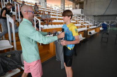 Trener podaje koszulkę zawodnikowi klubu pływackiego, w tle trybuny Hali Sportowej.