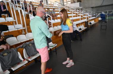 Trener podaje koszulkę zawodniczce klubu pływackiego, w tle trybuny Hali Sportowej.