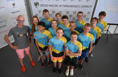 Grupa dzieci z klubu pływackiego z trenerem, w strojach sportowych, ujęcie z góry.