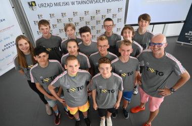 Grupa dzieci z klubu pływackiego z trenerem, w koszulkach I love TG, ujęcie z góry.