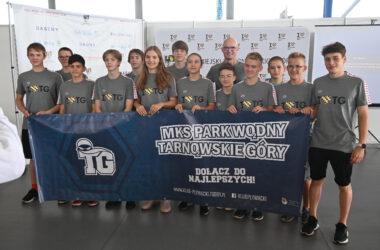 Grupa dzieci z klubu pływackiego trzyma przed sobą duży baner klubowy.