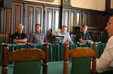 Pięciu mężczyzn na spotkaniu. sali sesyjnej Ratusza