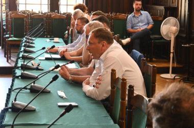 Osiem osób przy stole na sali sesyjnej Ratusza