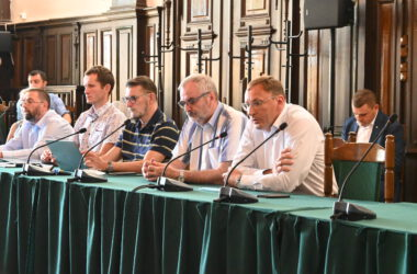 Siedem osób przy stole na sali sesyjnej Ratusza