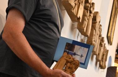 Jerzy Lisek trzymający małą drewnianą rzeźbę