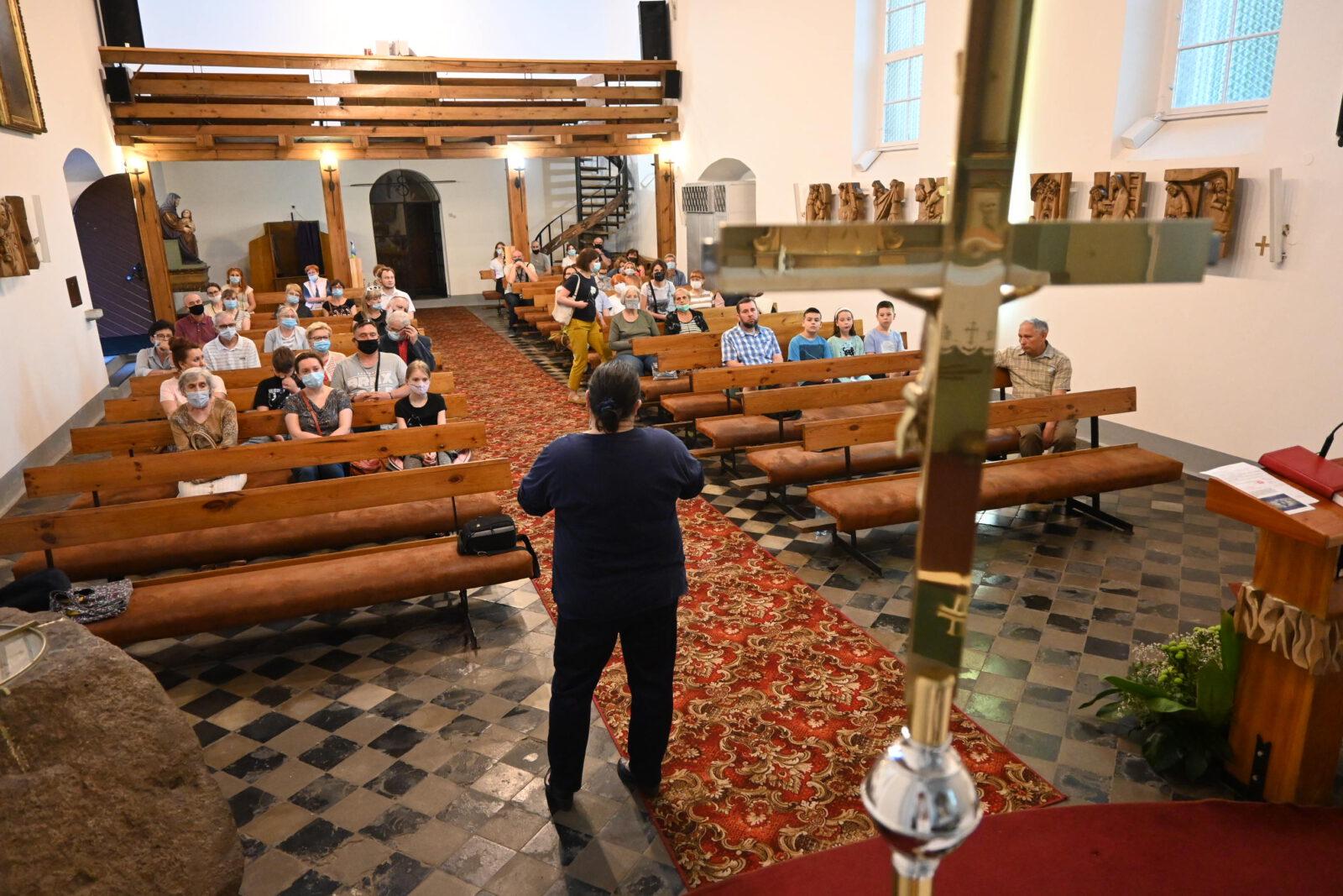 Wnętrze kościoła św. Anny z ludźmi siedzącymi w ławkach.