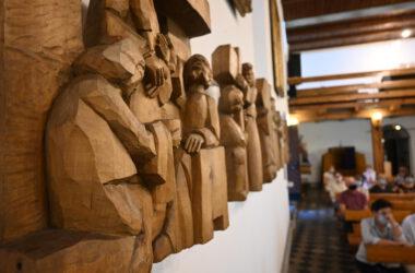 Drewniana, rzeźbiona stacja krzyżowa zawieszona na ścianie kościoła świętej Anny