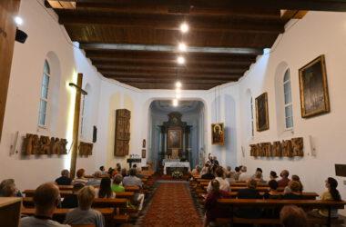Wnętrze kościoła św. Anny, z drewnianym stropem i ludźmi siedzącymi w ławkach.