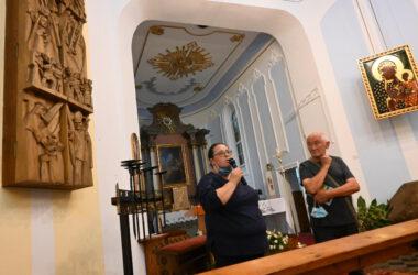 Wnętrze kościoła, po lewej stronie drewniana naścienna stacja drogi krzyżowej, po środku dwie osoby, po prawej stronie obraz Matki Boskiej