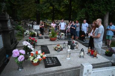 Grupa osób zwiedzających cmentarz