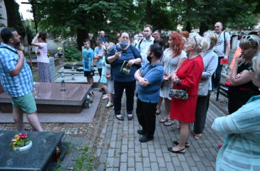 Grupa osób zwiedzających cmentarz.