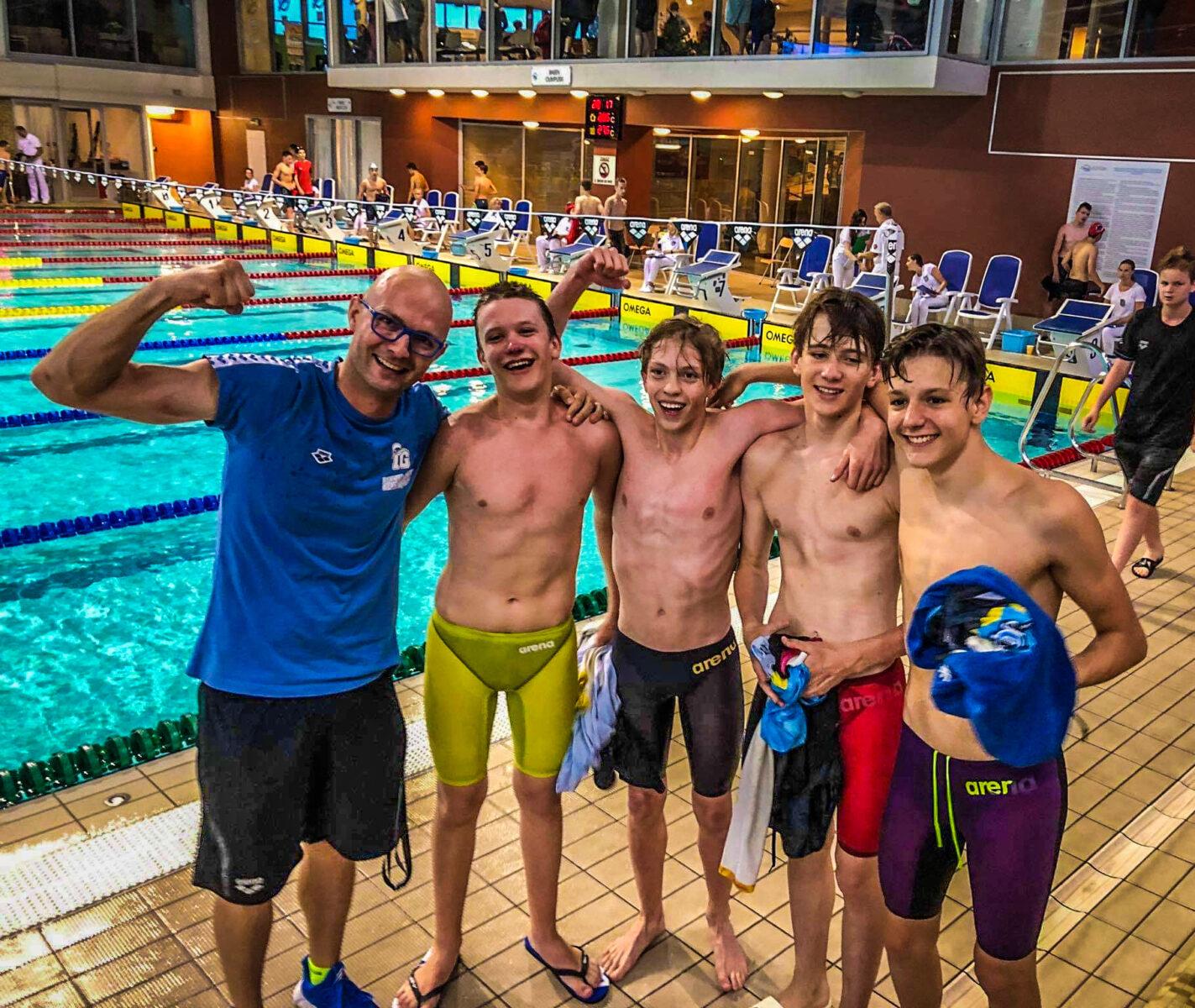 Trener z czterema zawodnikami na tle basenu