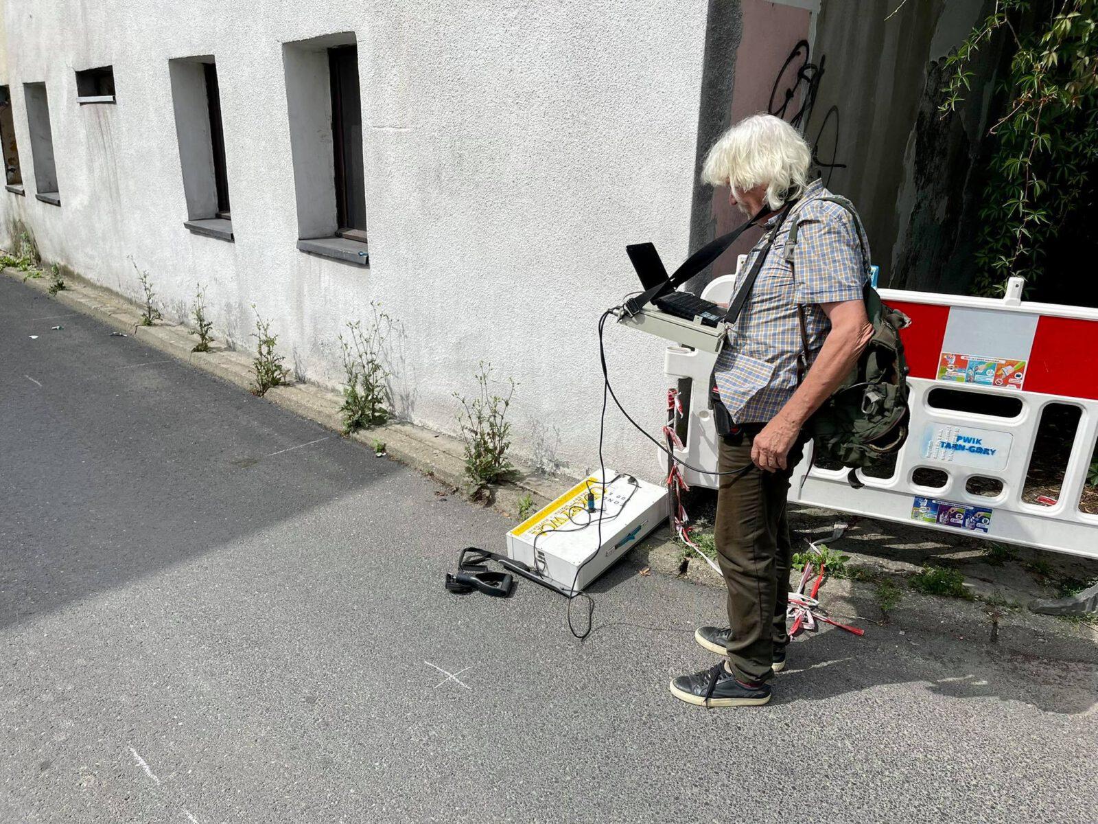 Mężczyzna z georadarem przy ścianie budynku.