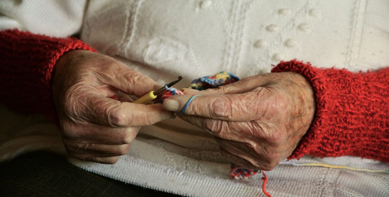 Zbliżenie dłoni seniorki z szydełkiem