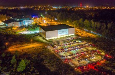 Kino samochodowe przed Halą Sportową z lotu ptaka nocą.
