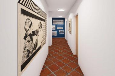 Biały korytarz zakończony niebieską ścianą z grafikami i ceglaną podłogą