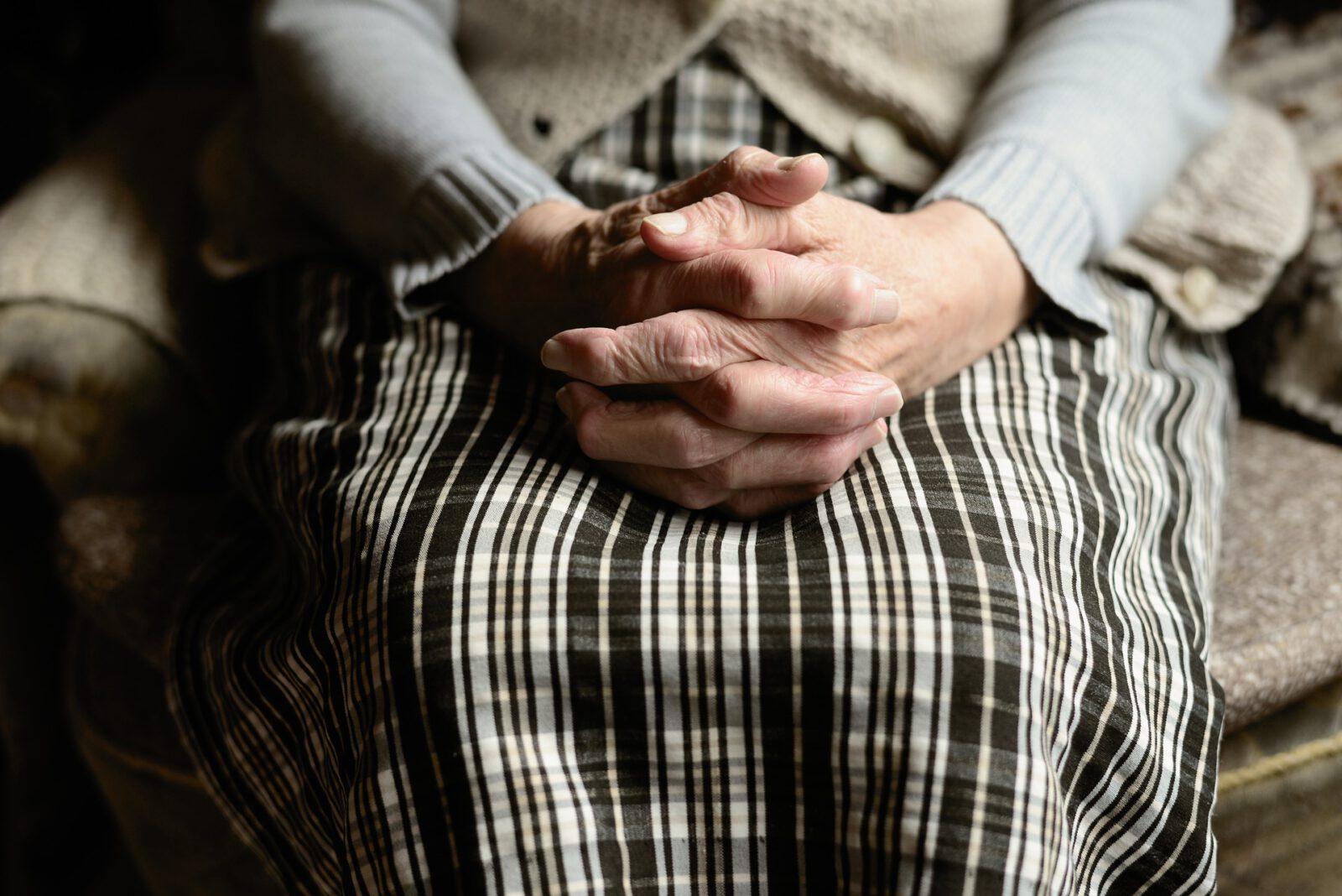 Zbliżenie splecionych dłoni seniorki