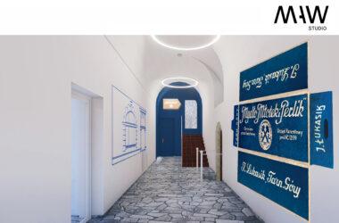 Biały korytarz z biało niebieskimi ścianami i grafikami.