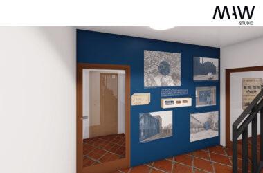 Sala z grafikami na niebieskiej ścianie.