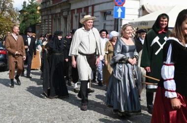 Osoby przebrane za postacie historyczne wchodzą na rynek.