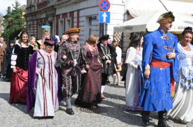 Osoby przebrane za postacie historyczne wchodzą na rynek. Na pierwszym planie postać Jana III Sobieskiego z Marysieńką.