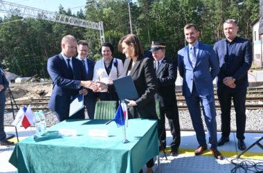 Akt podpisania umowy na peronie w Herbach Nowych. W tle grupa osób.
