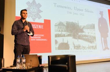 Na scenie Marek Panuś z prezentacją w tle.