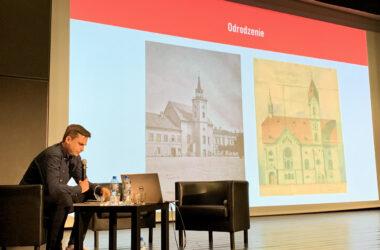 Na scenie Marek Panuś, w tle prezentacja z kościołem ewangelickim.