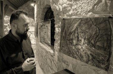 Mężczyzna ogląda prace Radosława Krzyżowskiego.