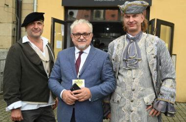 Burmistrz Arkadiusz Czech z dwoma mężczyznami przebranymi za postacie historyczne.