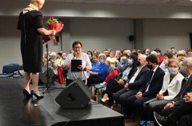 Pani Magdalena Latacz n scenie z bukietem kwiatów a przed sceną zgromadzona publiczność.
