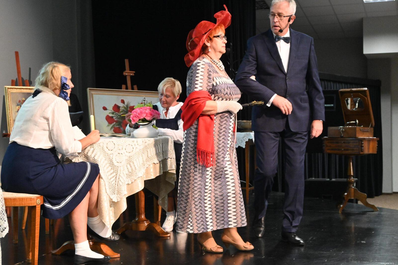 """Członkowie stowarzyszenia odgrywający fragment """"Moralności Pani Dulskiej"""". Dwie kobiety siedzą przy stoliku a przed nimi kobieta w dużym, czerwonym kapeluszu i mężczyzna w garniturze."""