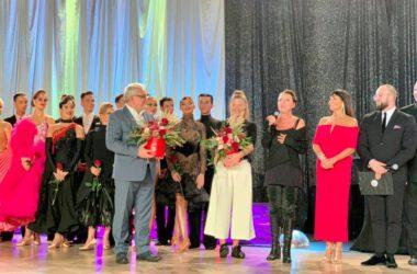 Burmistrz Arkadiusz Czech z kwiatami wśród jurorów i tancerzy na gali tańca towarzyskiego.