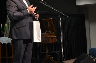 Burmistrz Arkadiusz Czech na scenie przed mikrofonem z prezentem dla Stowarzyszenia Uniwersytet Trzeciego Wieku.