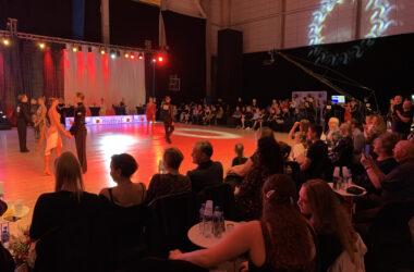 Publiczność uczestnicząca w gali z tancerzami w tle.